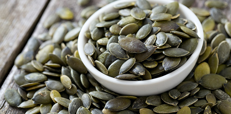 A bowl of pumpkin seeds with some of the table beside