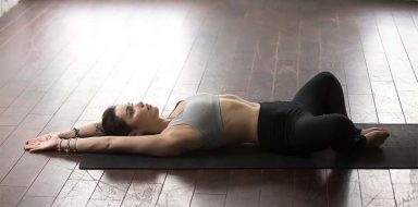 A girl in a sport bra and yoga pants doing the cobbler's pose on a yoga mat.