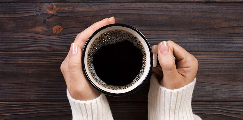 Someone holding a mug of coffee against dark brown hardwood.